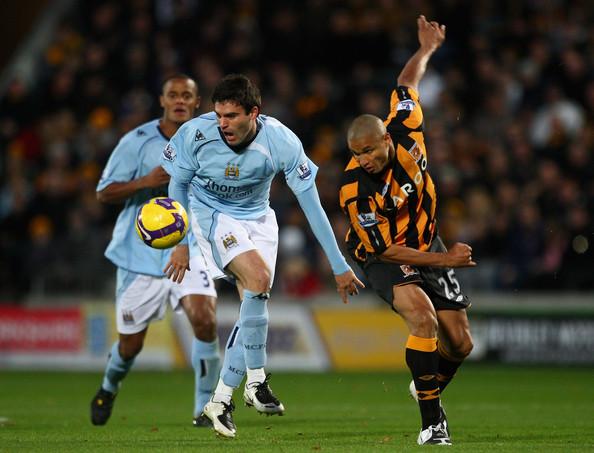 Manchester City tegen... Hull, schat ik zo. Ofwel: hemelsblauwe koningsmantel van de weemoed versus gek wespenpakje.
